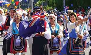 people in Greek national costume waving Australian and Greek flags in a parade